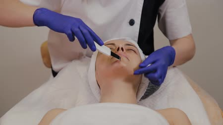 soyulması : Professional beautician does ultrasonic face cleaning for middle-aged woman. Stok Video