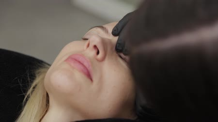 folt : A professional beautician in a beauty salon performs eyelash lamination procedure.