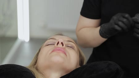 глина : A professional beautician in a beauty salon performs eyelash lamination procedure.