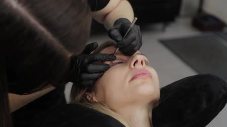 pflaster : A professional beautician in a beauty salon performs eyelash lamination procedure.