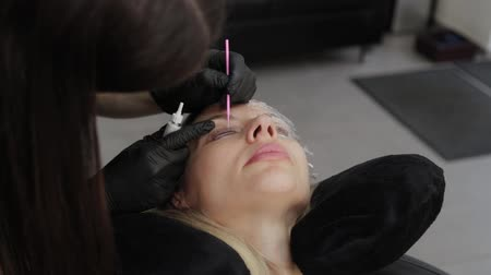 folt : A professional cosmetologist in a beauty salon applies eyelash lamination gel to the client s eyelashes.