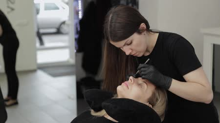 cabinet : A professional beautician in a beauty salon performs eyelash lamination procedure.