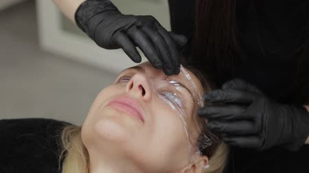 film camera : Professional beautician in a beauty salon closes the eyes of the client with a special film. Stock Footage