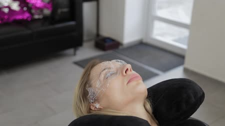 適用する : Beautiful woman with film on her eyes in a beauty parlor.