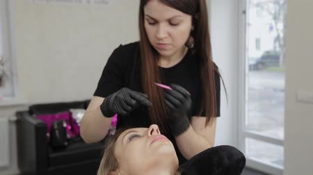 longer : Professional beautician in a beauty salon straightens eyelashes to a client.