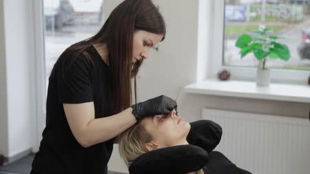 csipesz : Professional beautician in a beauty salon straightens eyelashes to a client.