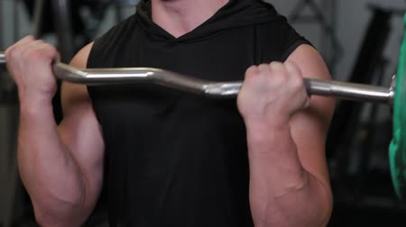 construção muscular : Professional athlete trains barbell biceps.