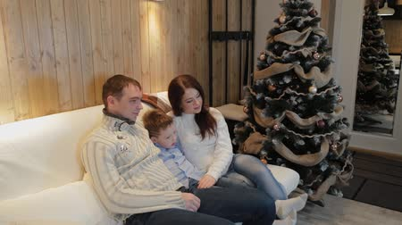 father christmas : Beautiful happy family of three on the sofa smiling and talking by the Christmas tree on Christmas night.
