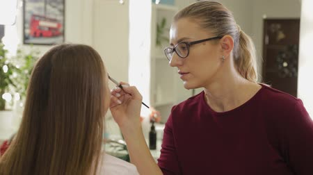 alapítvány : Professional eye makeup. Stylist makeup artist applies makeup to a young woman with a special brush in a beauty salon.