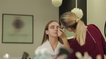 eyeshade : Professional makeup artist puts eye shadow on a client of a beauty salon.