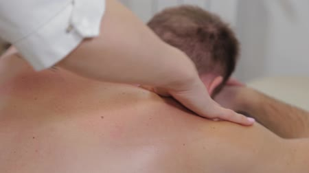 ból pleców : Professional woman masseur doing massage on the back of a man. Massage at the beauty salon. Wideo