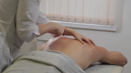 массаж : Professional woman masseur doing massage on the back of a man. Massage at the beauty salon. Стоковые видеозаписи
