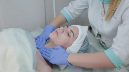 professional wellness : Professional beautician woman rubs her face before the procedure with wet wipes. Stock Footage