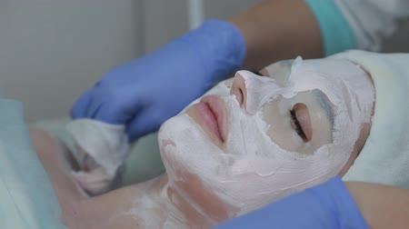 eye mask : Professional cosmetologist woman removes mask from clients face with wet wipes. Stock Footage