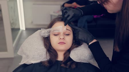 fixação : Professional master eyebrow woman removes the film from the eyebrow and removes liquid on the eyebrows in a beauty salon. Vídeos