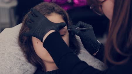 eyebrow correction : Professional master eyebrow woman plucking eyebrows with tweezers to client in beauty salon. Stock Footage