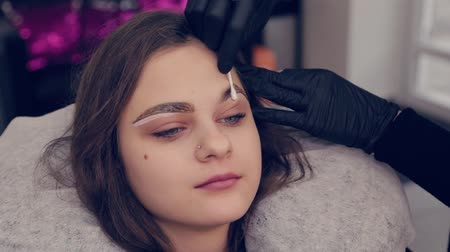 cotton swab : Professional woman eyebrow master handles a cotton bud with eyebrows to client in beauty salon.