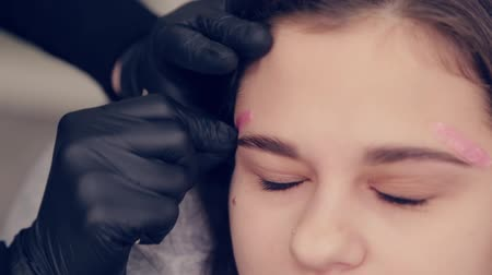 eyebrow correction : Professional master eyebrow woman doing depilation with wax eyebrow to client to client in beauty salon.