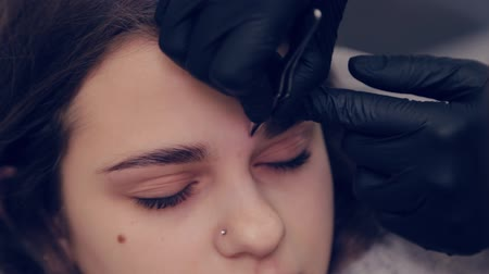 tweezing : Professional master eyebrow woman plucking eyebrows with tweezers to client in beauty salon. Stock Footage