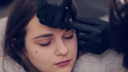 brow : Professional master eyebrow woman plucking eyebrows with tweezers to client in beauty salon. Stock Footage