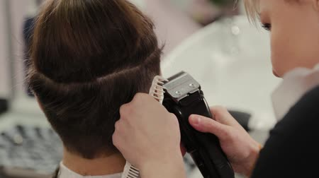 barber hair cut : Professional hairdresser woman cutting hair to client with hair clipper.