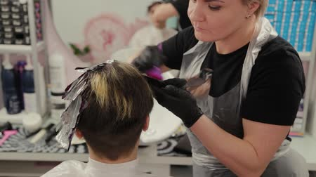 vlasy : Professional hairdresser woman washes hair dye girl.
