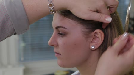 diadeem : Professional hairdresser puts a hairpin on the head of a girl.
