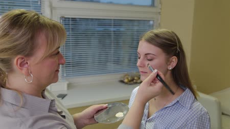 alapítvány : Professional make-up artist applies foundation on face to client.
