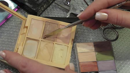 aplikatör : Professional makeup artist picks up an iron spatula cream on a palette for applying to the face. Stok Video