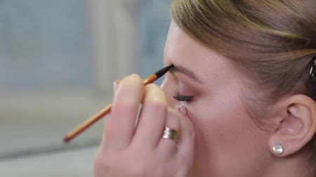 kaşları : Professional makeup artist paints eyebrows to the client with a special brush.