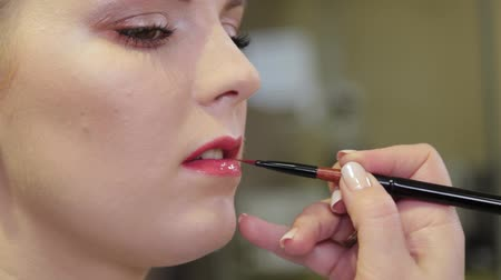 model s : Professional make-up artist applying lip gloss on client s lips with a brush.