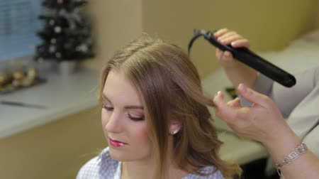 curling hair : Professional hairdresser doing evening hairstyle for girl.