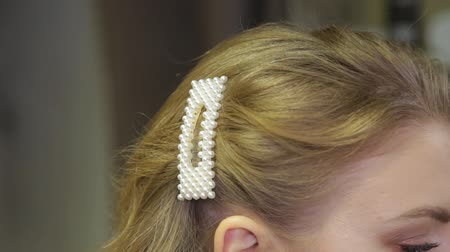çelenk : Professional hairdresser puts a hairpin on the head of a girl.