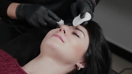 remover : Professional permanent makeup master removes makeup from the face with cotton pads to the client.