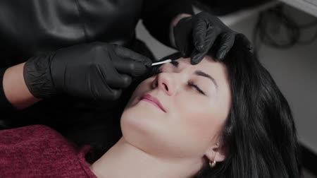 zalf : Professional permanent make-up artist apply anesthetic on the eyebrows of the client.