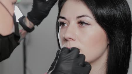 eyebrow correction : Professional permanent make-up artist does eyebrow marking for a client. Stock Footage