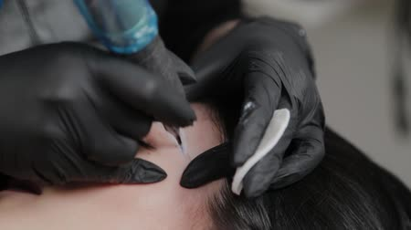 microblading : A professional permanent makeup artist does permanent eyebrow makeup with a tattoo machine.