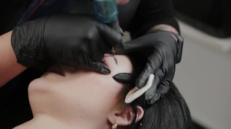 corrections : A professional permanent makeup artist does permanent eyebrow makeup with a tattoo machine.