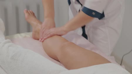 cellulite treatment : Female massage therapist doing massage over the entire length of the legs of a young girl. Stock Footage