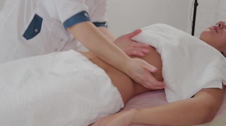 strandlaken : Woman massage therapist does massage on the stomach of a young girl. Stockvideo