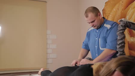 masażysta : Professional male masseur makes a vacuum massage with a special device to a beautiful woman.