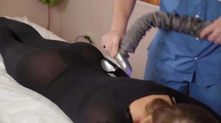 liposukcja : Professional male masseur makes a vacuum massage with a special device to a beautiful woman.