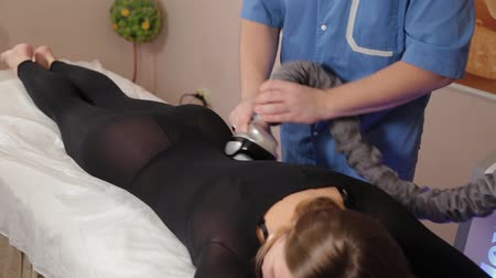 целлюлит : Professional male masseur makes a vacuum massage with a special device to a beautiful woman.