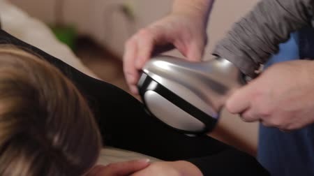 apparatus : Professional male masseur makes a vacuum massage with a special device to a beautiful woman.