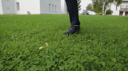 looking for : Legs of a man in trousers walking on the grass.
