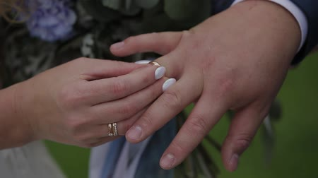 церемония : The groom puts the wedding ring on finger of the bride. marriage hands with rings. The bride and groom exchange wedding rings. Стоковые видеозаписи