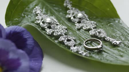 кулон : Beautiful earrings and a gold engagement ring on a wet green leaf.