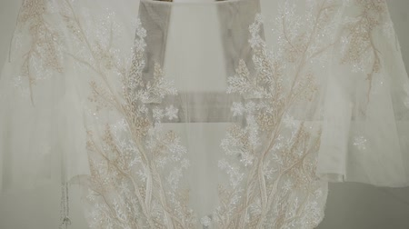 vállfa : Beautiful modern wedding dress hanging in the house.