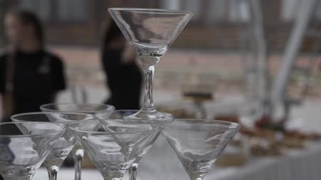 martini glasses : The waiter puts a pyramid of champagne.