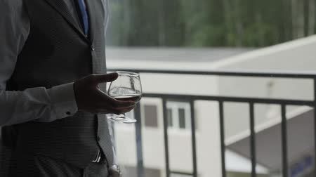 bourbon whisky : Male businessman with a glass of whiskey by the window. Stock mozgókép
